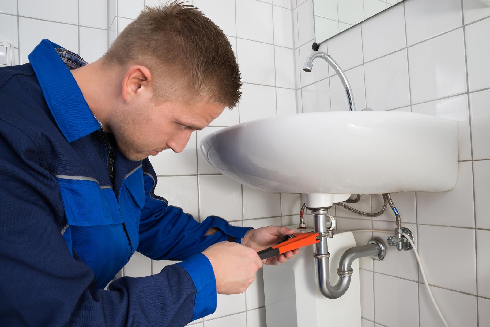 bigstock Male Plumber Fixing Sink In Ba 118654115